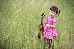 De viool van het jonge geitjesspel in struiken Royalty-vrije Stock Afbeeldingen