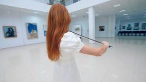 De vioolspeler presteert in een museum, die zich in een ruimte met schilderijen bevinden stock videobeelden