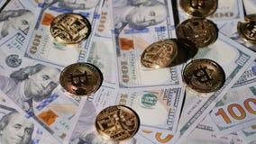 De virtuele muntmuntstukken bitcoin vallen op de achtergrond van dollars de V.S. langzame geanimeerde video stock video