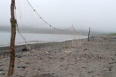 De visnetten drogen op het strand in mistig weer stock foto's