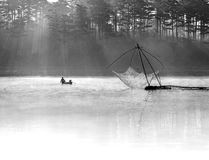 De vissen van de vissersmens uit op het meer het hulpmiddel van de vissersman, zij die dit voor hun baan, in mistig gebruiken Stock Foto's