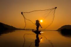 De vissen van de vissersvangst in de ochtend Stock Afbeelding