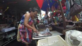 De vissen van het verkopersontkalken bij stoep blokkeren natte markt stock videobeelden