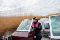 De visser berijdt een boot bij snelheid op een smalle rivier in het struikgewas van riet royalty-vrije stock fotografie
