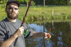 De visser bevindt zich over het water en toont een reeks voor het vangen van levende vissen stock afbeeldingen