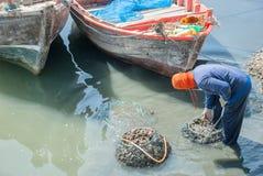 De visser brengt mosselen in het net doorweekt het water Royalty-vrije Stock Afbeelding