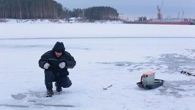 De visser in donkere de winterkleren bereidt haak met aas voor en treft voor de winterijs vissend voorbereidingen op bevroren riv stock footage