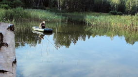 De visser drijft op de rivier in een opblaasbare boot De camera kijkt uit berk Activiteiten in de wildernis stock footage