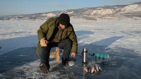 De visser is een mens in de winter visserij stock footage