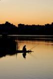 de visser en de zonsopgang over het water Royalty-vrije Stock Afbeeldingen