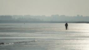 De visser gaat op de bevroren rivier in de winter De zon glanst Achter de kinderen is er een groot wit zeil royalty-vrije stock afbeeldingen