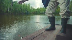 De visser houdt catched zalmvissen op de haak in zijn handen stock videobeelden