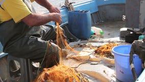 De visser is lege vis van netto in zijn kleine boot stock footage