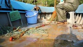 De visser is lege vis van netto in zijn kleine boot stock videobeelden