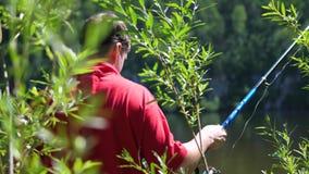 De visser met een hengel is op de rivierbank Mooi de zomerlandschap Openlucht recreatie hobby stock footage