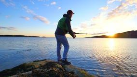 De visser met groene sportieve rugzak controleert vistuigen De mens bereidt duwend aas op vislijn voor en werpt lokmiddel stock video