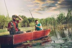 De visser met zoon onderzoekt het water omdat zij hun vangst verloren stock foto
