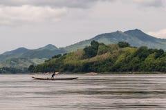 De visser op de boot in evenwicht wordt gehouden lanceert het net op de Mekong Rivier, Luang Prabang, Laos dat stock foto
