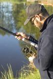 De visser past de rem op het spinnewiel aan terwijl status over het water stock foto's