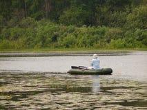 De visser van de hengelsport in een boot royalty-vrije stock fotografie