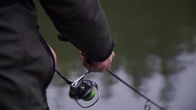 De visser verdraait spinnende spoel en vangstforel stock videobeelden