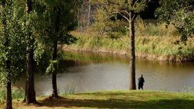 De visser vist in kalm rivierwater dichtbij de kust stock video