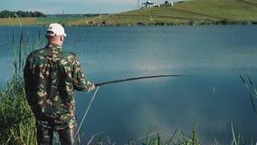 De visser wacht, dan trekt gevangen vissen terug stock videobeelden
