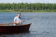 De visser zit in een boot op de rivier en vangt vissen voor een aas, een weekend in aard stock foto