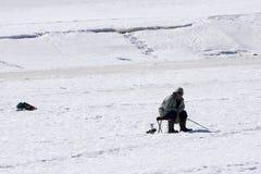 De visser zit en vangt vissen op een stoel op het ijs in gevoelde laarzen in de winter - Rusland Berezniki 7 April 2018 stock afbeeldingen
