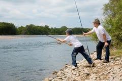 De visserij van de grootvader en van de kleinzoon stock fotografie