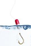 De visserij van haak met medische pil als vlotter in water royalty-vrije stock afbeeldingen