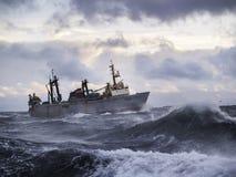 De visserij van schip in sterk onweer. stock afbeeldingen