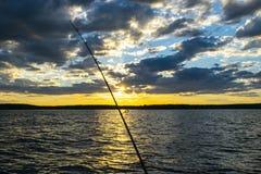 De visserij van wegsilhouet tijdens zonsondergang Hengel tegen oceaan bij zonsondergang Hengel in een zoutwaterboot tijdens visse royalty-vrije stock foto's