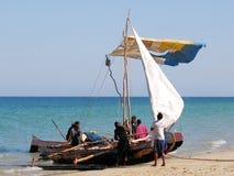 De visserijkano van Madagascar op het strand met vissers Stock Afbeelding