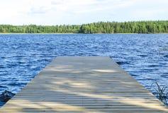 De visserijpijler bij het meer in landelijk Finland Houten pijler bij blauw water en groen bos op zonnige dag Houten pierbrug stock afbeelding