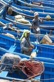 De vissers bevinden zich onder een overzees van boten in de haven in Essaouira in Marokko Stock Foto