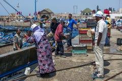 De vissers maken hun vangst van een treiler bij de bezige haven leeg in Essaouira in Marokko Stock Foto's