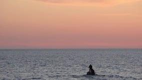 De vissers op de boot werpen het net in het overzees bij de achtergrond van de zonsonderganghemel stock videobeelden