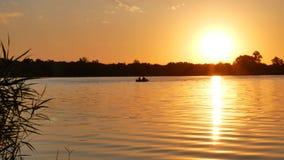 De vissers varen in een boot op het meer stock video