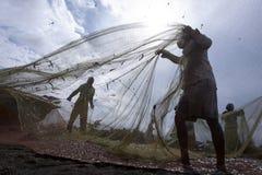 De vissers verwijderen vissen uit hun netten na het terugkeren van van nachten vissend van Negombo in Sri Lanka Stock Afbeelding