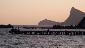 De vissers zitten op het dok en de vangstvissen bij zonsondergang Royalty-vrije Stock Foto's