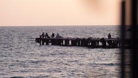 De vissers zitten op het dok en de vangstvissen bij zonsondergang Stock Foto's