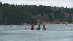 De vissers zitten op het ijs en de vissen stock video