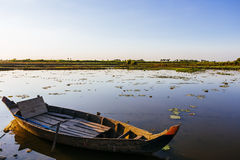 De vissersboot bij het meer van het lotusbloemlandbouwbedrijf in Kambodja bij zonsondergang Royalty-vrije Stock Foto