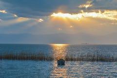 De vissersboot en de stilte van de zonsondergangtijd stock fotografie