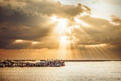 De vissersboot op het zeewater en de zonnestraal is achtergrond royalty-vrije stock afbeelding
