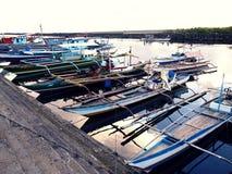 De vissersboten dokken bij bij vissenhaven of pijler en vullen hun levering uit vóór rubriek bij aan overzees opnieuw Royalty-vrije Stock Foto's