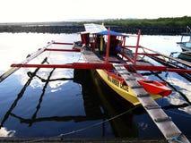 De vissersboten dokken bij bij vissenhaven of pijler en vullen hun levering uit vóór rubriek bij aan overzees opnieuw Royalty-vrije Stock Afbeelding