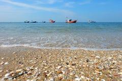 De vissersboten liggen bij anker door overzees, en Strand en kleurrijke shells royalty-vrije stock afbeelding