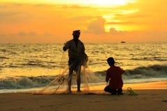 De vissersfamilie bereidt hun familie van fisvissers voorbereidt voor hun visnet tijdens zonsondergangtijd hing netto tijdens zon Royalty-vrije Stock Fotografie